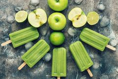 Green popsicles on a rustic background with apple and lime. Summer refreshing dessert.Flat lay, view from above.Toned photo. Green popsicles on a rustic royalty free stock images