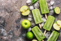 Green popsicles on a wooden background. Frozen juice on a stick, green apple, lime.Flat lay, top view. Green popsicles on a wooden background. Frozen juice on a stock photo