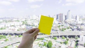Green sticky note put on urban scene with sky. By a hand Stock Image