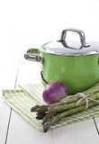 Green pot and asparagus. Green pot with a bunch of fresh green asparagus ans purple onion on green checkered napkin stock images
