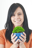 Green potted. Beautiful woman holding a green potted plant held in a pair of protective hands Royalty Free Stock Photography