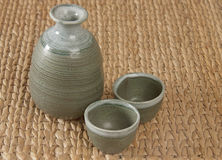 A green pottery tea set. On woven bamboo mat royalty free stock photography