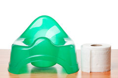 Green potty and toilet paper Royalty Free Stock Photos