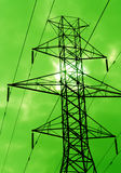 Green Power. The silhouette of power lines agains a green sky Royalty Free Stock Photos