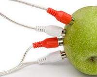 Green power. A green apple with audio or power connections coming out of it royalty free stock photo