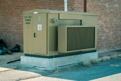 Green power generator outside brick building. A green power generator outside a brick building in the background royalty free stock photos