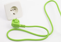 Green power plug and outlet. Green power plug into power outlet against a white background stock photos