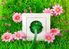 Green power plug into outlet on the grass Stock Photo