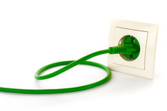 Green power plug into power outlet royalty free stock photography