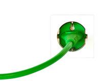 Green power plug in simple wall outlet. Against white background stock photo