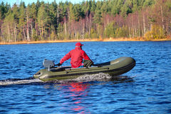 Green, powerboat, inflatable rubber boat with motor on wood lake Royalty Free Stock Image