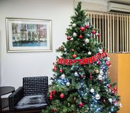 Green Pre Lit Christmas Tree With Baubles Stock Photography