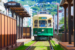 Green Public tram moving along the railway. Nagasaki city, Japan. Stock Photos