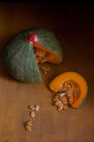 Green pumpkin with stem covered with red wax , cut into wedges Stock Photo