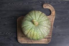 Green pumpkin on a wooden background. Still life - Green pumpkin on a wooden background Stock Photos