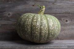 Green pumpkin on a wooden background. Still life - Green pumpkin on a wooden background Stock Photo