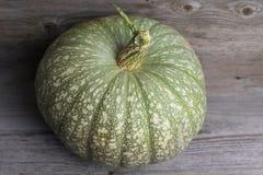 Green pumpkin on a wooden background. Still life - Green pumpkin on a wooden background Stock Image