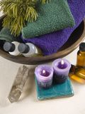 Green and purple bath. Green and purple towels in a wooden bowl with candles, a crystal wand and massage oils on the side Royalty Free Stock Photography