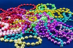 Green, purple, and gold mardi gras beads on blue stock photo