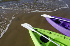 Green and Purple Kayaks on Beach Stock Photos