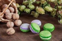 Green and purple macaroons. Rustic scene. Green and purple macaroons with walnuts on wooden background. Rustic scene. Shallow focus stock photo