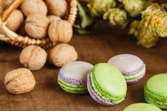 Green and purple macaroons. Rustic scene. Green and purple macaroons with walnuts on wooden background. Rustic scene. Shallow focus stock photos