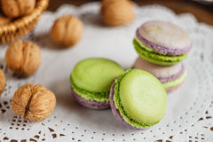 Green and purple macaroons. Rustic scene. Green and purple macaroons with walnuts on wooden background. Rustic scene. Shallow focus royalty free stock photos