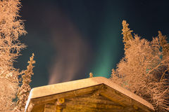 Green and purple Northern Lights above cabin Stock Photo