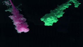 Green and purple paint dropping in water on black background. In slow motion stock video footage