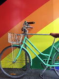 Green Pushbike and Rainbow Wall. A pastel green pushbike, or bicycle, leaning against a brightly rainbow coloured wall Royalty Free Stock Photo