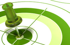 Green pushpin on target. Green pushpin on center of a target symbol of reaching objectives Royalty Free Stock Images