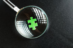 Green puzzles and magnifying glass Royalty Free Stock Images