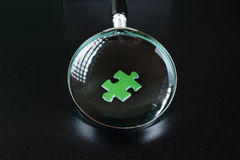 Green puzzles and magnifying glass Stock Image