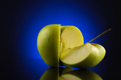 Green quarter and three quarters apple on blue Royalty Free Stock Photo