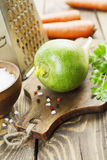 Green radish and carrot. Fresh green radish and carrot on the wooden table Stock Images