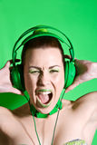 Green rage. Beautiful woman with headphones screaming very loud Royalty Free Stock Images