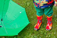 Green rain umbrella and children autumn boots Stock Photos