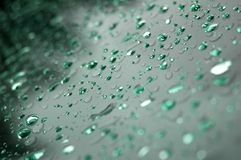 Green raindrops. On the front screen of a car Stock Photo