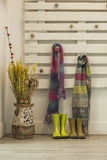Green rainy boots and colorful scarfs hanging in a pallet wall. Royalty Free Stock Image