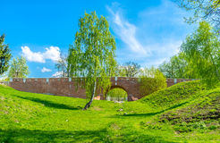 In the green ravine. The walk along the sunny ravine with the view on Greenhouse Bridge between the Royal Greenhouses and Bread House, Tsaritsyno, Moscow, Russia Royalty Free Stock Image