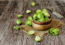 Green raw Brussels sprouts in wooden bowl , selective focus. Green raw Brussels sprouts in a wooden bowl on a rustic wooden table, selective focus Stock Photo