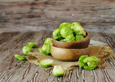 Green raw Brussels sprouts in wooden bowl , selective focus. Green raw Brussels sprouts in a wooden bowl on a rustic wooden table, selective focus Stock Photography