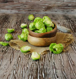 Green raw Brussels sprouts in wooden bowl , selective focus. Green raw Brussels sprouts in a wooden bowl on a rustic wooden table, selective focus Stock Images