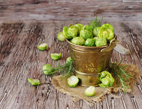 Green raw Brussels sprouts in wooden bowl , selective focus. Green raw Brussels sprouts in a wooden bowl on a rustic wooden table, selective focus Stock Photos