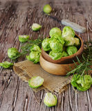 Green raw Brussels sprouts in wooden bowl , selective focus. Green raw Brussels sprouts in a wooden bowl on a rustic wooden table, selective focus Stock Image