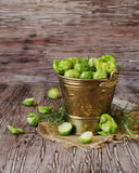 Green raw Brussels sprouts in wooden bowl , selective focus. Green raw Brussels sprouts in a wooden bowl on a rustic wooden table, selective focus Royalty Free Stock Images