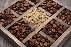 Green (raw) coffee and roasted coffee beans Royalty Free Stock Photo