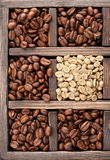 Green (raw) coffee and roasted coffee beans Stock Photos