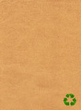Green recycle sign on brown paper. Background Stock Images