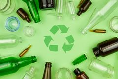 Green recycle sign symbol with glass trash garbage. Bottle, pills and tubes on green isolated background. Ecology recycle, environment issue, safe planet royalty free stock image